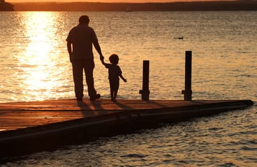 Man and child on a pier at sunset.