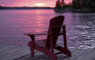 Deck chair on a lake pier at sunset.