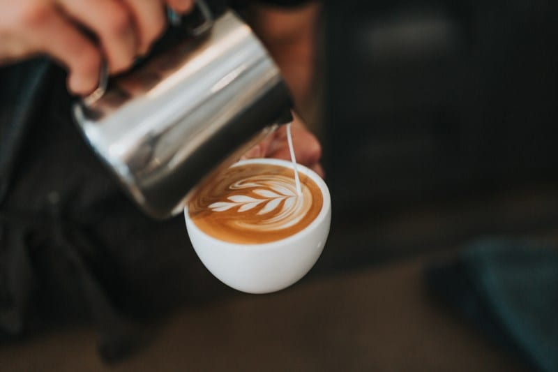 Close up of person pouring milk into a latte mug.