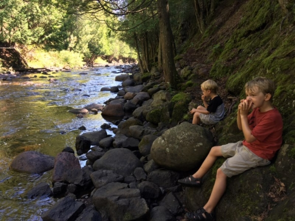 Boys sitting at a rocky riverside.