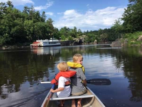 Two kids in a boat on a lake.