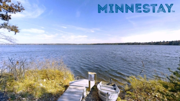 Lakefront dock and boat. Text: Minnestay.