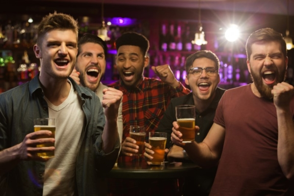 Men at a bar with beers.