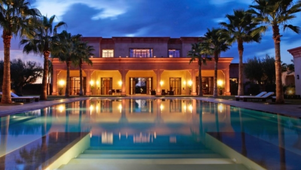 Italian villa with pool and palm trees.
