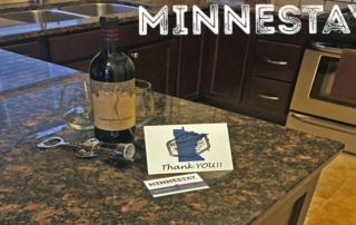 Wine bottle and Minnestay card on kitchen counter.