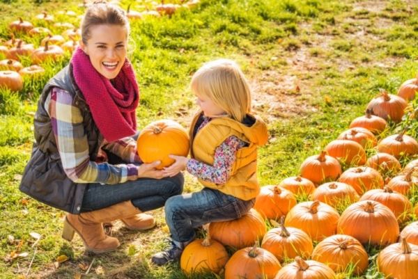 Woman and child with pumpkins.