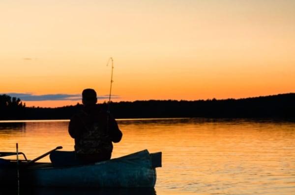 Main in a boat fishing at dawn.