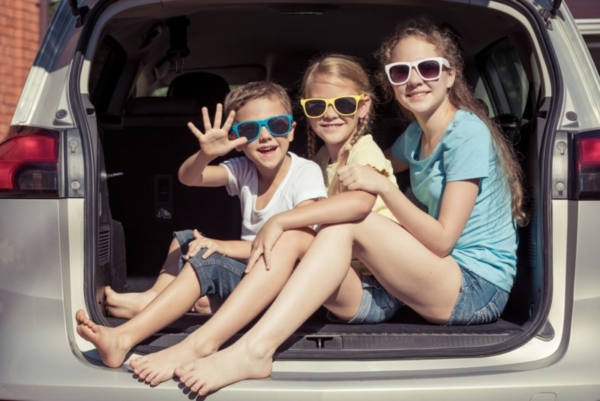 Kids sitting in a van trunk.