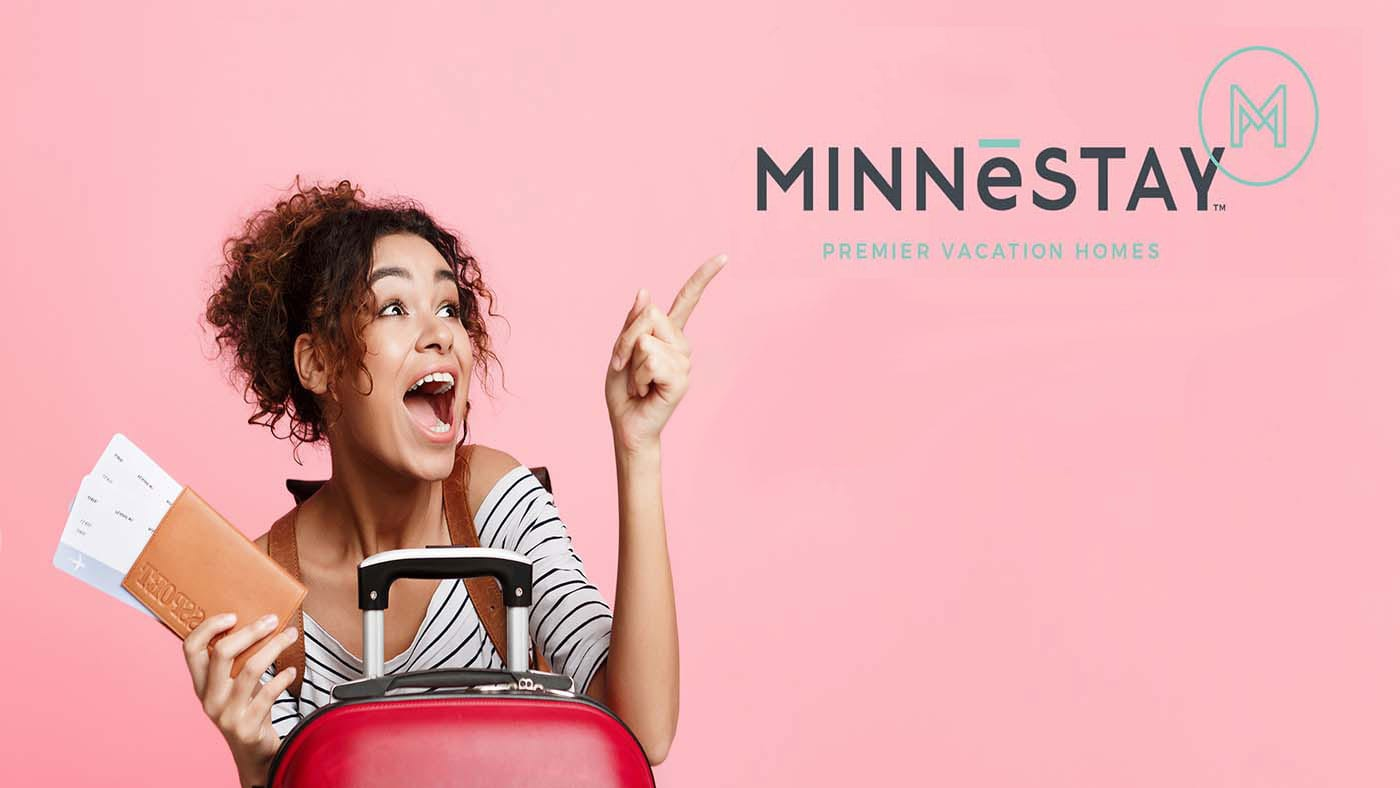 Excited woman with tickets pointing finger away. Text: Minnestay, Premier Vacation Homes.