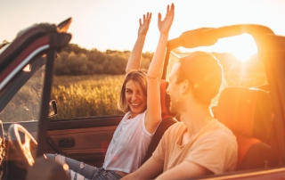 Woman hold hands up as man drive convertible both smiling